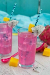 Two glasses with straws decorated with dragonfruit and filled with a bright pink drink